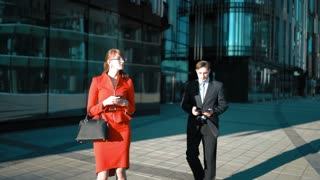 Young businessman in suit and tie make an offer with tablet PC to brown hair sexy attractive businesswoman in red dress and glasses. She agree smile and shake hand. Glass business centre. UltraHD 4k