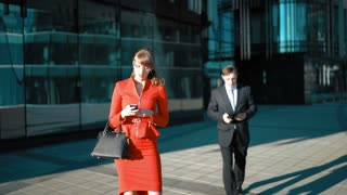 Young businessman make an offer with tablet PC to brown hair sexy attractive businesswoman in red dress. Handshake. Glossy district bg wide shot. Sunny day