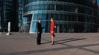 Young cheerful Business partners man and woman doing a handshake in suit outdoor. Glass modern office building district bg. Slow motion wide shot. Teal and orange