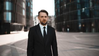 Young confident successful attractive businessman exult of Your business and applause with beard and mustache, Success concept. Formal black suit, tie. Modern glass buildings district bg. Sunrise