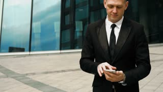 Young European business-man in black suit and tie smiling and talking by smartphone. Modern business-centre building at the background. Teal and Orange style. Close-up 4k flycam shot