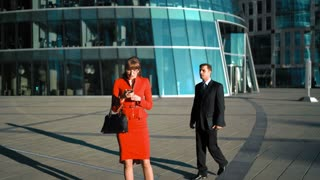 Young pretty sexy businesswoman in red dress talking smartphone. Businessman in suit and tie shy to contact with female outdoor in business glass building district. 4k ultra hd. wide shooting