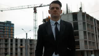 Young seriously successfiul customer Businessman in black suit walk checking and opening digital pad near new construction with crane and beams at background. Middle steadicam shot