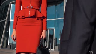 Young sexy successful brown hair businesswoman with spectacles in red dress suit and businessman shaking hands outdoor. Middle shot in super slow motion