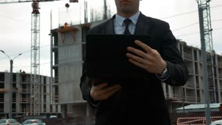 Young strong successfiul customer businessman in black suit walk alone checking and using digital pad near new construction with crane and beams at background. Middle steadicam shot