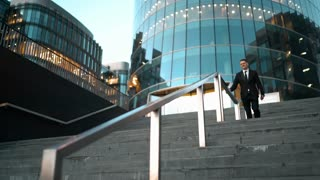Young successful businessman easy slide on the outdoor stairs rail with smile and jump at the end. Glass business centre building at the background. Teal and Orange style. Wide Ultra HD tripod shot