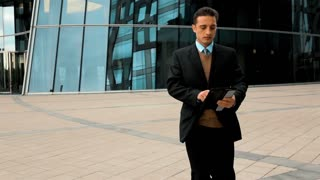 Young successful businessman in black suit and blue shirt brown vest and tie goes to work and uses black tablet PC for Internet serfing. Modern glass business centre at the background. Teal and orange