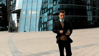 Young successful businessman in black suit and blue shirt brown vest and tie goes to work and uses black tablet PC for Internet serfing. Modern glossy business centre at the background. Teal and
