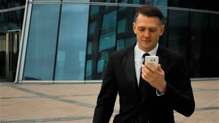 Young successful businessman in black suit and tie goes to work and uses white a smart phone for answering call. Modern glass business centre at the background. Teal and orange style. Super slow