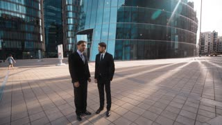 Young successful Businessman in formal suit recommed his confident collegue partner beard man in costume and tie to You. Modern glass business-centre building background. Teal and orange sunrise