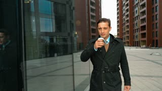 Young successful businessman walk with glass coffee in suit and cloak. He looking at his reflection at window with smiling. Fashion glossy business centre district at the background. Teal-and-Orange