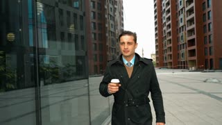 Young successful businessman walking with plastic glass coffee in suit and cloak. He looking at his reflection at window with smiling. Modern glass business centre building at the background. Teal and
