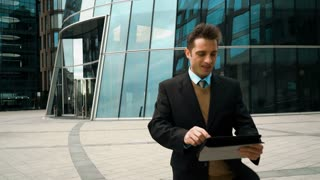 Young successful businessman walks and works with tablet-PC on the run. He interesting and smiling. Modern glass business centre building at the background. Teal and Orange style. Middle portrait 4k