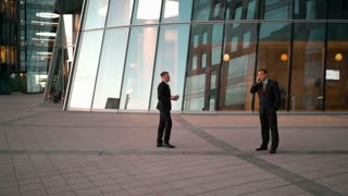 Young successful european businessman treat coffee cup his friend with tablet PC. Smiling conversation. Men going work together. Glass business-centre building at the background. Teal and Orange style
