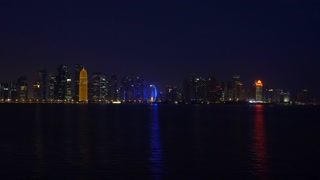 Doha Night City Reflecting in Sea Water of Persian Gulf, Real Time Video, Qatar, Middle East. Illuminated Skyscrapers on a West Bay reflected in a water of Gulf. View from MIA park