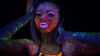 Portrait of Beautiful Woman with Purple Hair Dancing in Neon UV Light. Model Girl with Fluorescent Creative Psychedelic MakeUp, Moves Her Hand in Front of Face Defocused.