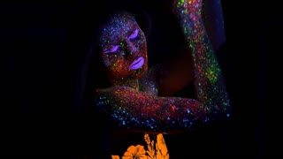 Portrait of Beautiful Woman with Purple Hair Dancing with Neon UV Light Lamp. Model Girl with Fluorescent Creative Psychedelic MakeUp, Art Design of Female Disco Dancer Model in UV