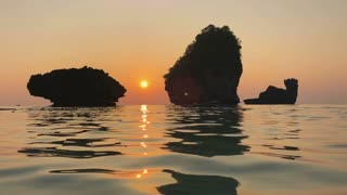 Romantic Sunset at Indian Ocean Coast. Rock Stones Rise Above the Water, Ripples on Sea Surface and Reflection of Cliff and Sun. Nui Bay, Phi-Phi, Krabi, Thailand.