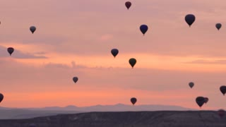 Silhouettes Lots of hot air balloons flying over valleys in Goreme, Turkey. Pink Dawn over the Incredible Place in Turkish Mountains.