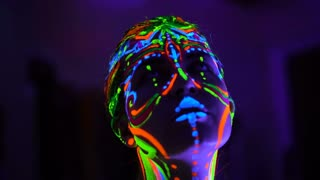 The bodyart ultraviolet painter draws on the face of Beautiful young sexy girl close up