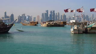 View on Doha Modern City Skyline. Day Shot, Qatar, Middle East. Traditional Wooden Qatar Boats with Qatar Flags at Corniche Broadway Coast in Clean Azure Water of Persian Gulf. Timelapse