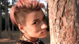 Young Pretty Punk Girl in Collar and Black Cloth with Pink Hair Hiding Behind the tree in Pine Forest at Sunset Time