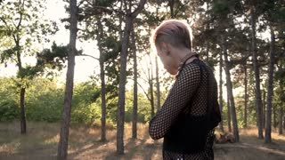 Young Pretty Punk Girl in Collar and Net. Pink Hair Girl walking in Pine Forest at Sunset Time