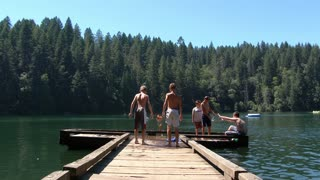 Boys Diving Off Dock At The Lake