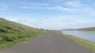 Female Cyclist Riding Bike Path