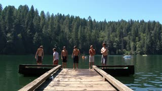 Group Of Kids Enjoy Summer Day At The Lake And Jump Off Dock