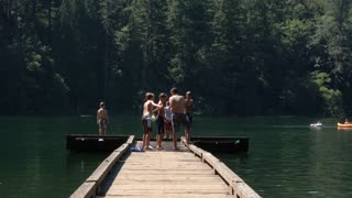 Happy Kids Jumping Off Dock Into Lake