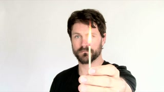 Man Lighting Matchstick In Studio