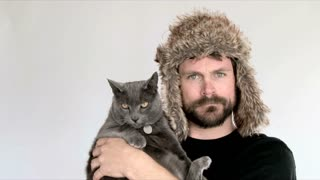 Man Wearing Funny Hat Holding Cat In Studio