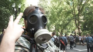 Person In Gas Mask Giving The Peace Sign