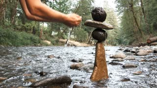 Pouring Water On Balanced River Rocks Slow Motion