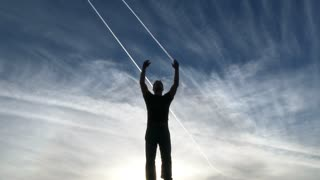 Silhouetted Person With Arms Raised To Blue Sky