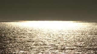 Sun Reflecting On Sea With Dark Horizon