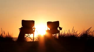 Two Empty Beach Chairs At Sunset