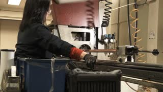 Woman Working Drill Press In Machine Room