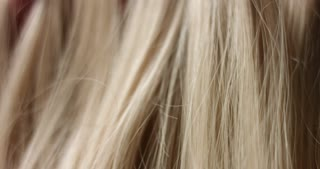 A woman's hand with bright manicure running through long wavy blond hair