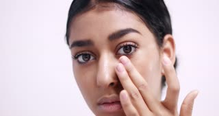 Applying eye cream in small dots under eyes and gently massaging it in isolated on white