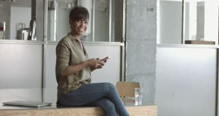 Attractive casually dressed black female in an industrial style office sitting on the desk with a smartphone