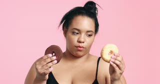 Attractive curvy black girl eating donuts and loving it on pink background