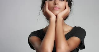 Attractive young Middle Eastern model touching her pretty face with flawless skin and smiling