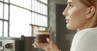 Attractive young woman wearing a white sweater in a loft style bakery or coffee shop with an ice latte in a glass