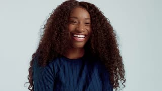 Beauty black mixed race african american woman with long curly hair and laughing. Happy laughing black woman on blue