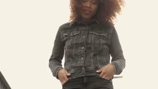 beauty black wman with big afro hair wears total denim look in cloudly day on bridge