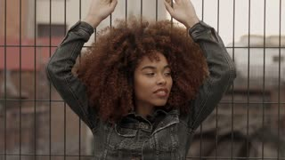black mixed race woman with big afro curly hair in urban industrial zone of city with train lines on background. Clouds autumn qtmosphere