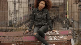 black mixed race woman with big afro curly hair sits on bench with graffity