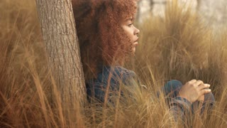 black mixed race woman with big afro curly hair sits on lawn with high grass on sunset. Denim look on hay